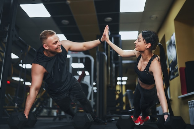 Casal forte e bonito de aptidão atlética em roupas de ginástica fazendo exercícios de flexão e dando-se mais cinco