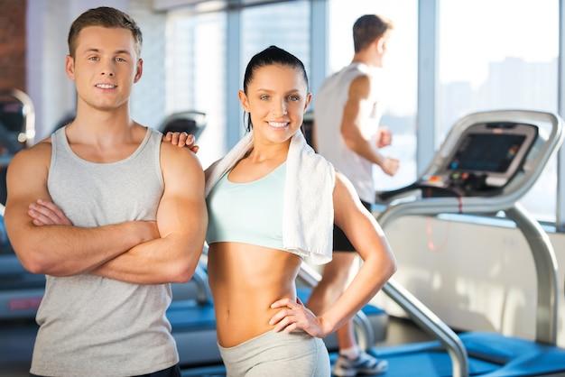 Casal forte e confiante. lindo casal jovem se unindo e sorrindo enquanto estava na academia com esteiras ao fundo