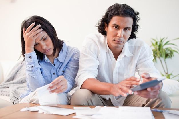 Casal frustrante verificando suas contas na sala de estar