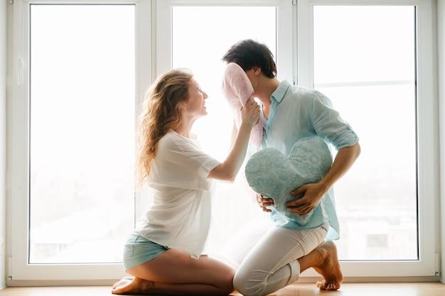 Casal garota e cara brincam com almofadas perto da janela. roupas brancas e azuis. dia dos namorados.