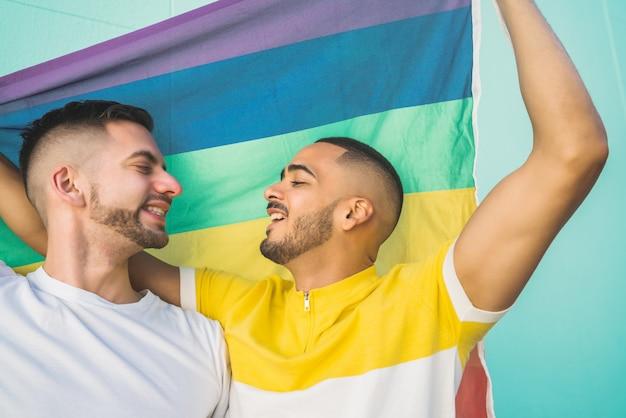 Casal gay abraçando e mostrando seu amor com a bandeira do arco-íris.