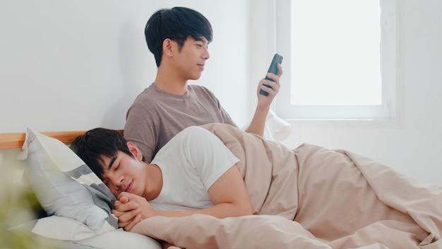 Casal gay asiático usando telefone celular em casa. jovem ásia lgbtq + homem feliz relaxar resto depois de acordar, verifique as mídias sociais enquanto seu namorado dorme deitado na cama no quarto em casa de manhã.
