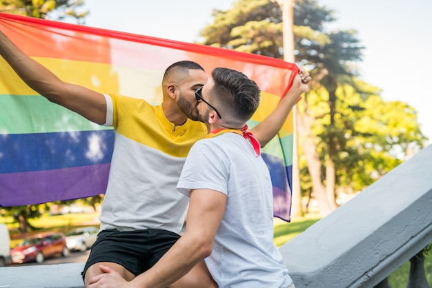Casal gay beijando e mostrando seu amor com a bandeira do arco-íris.