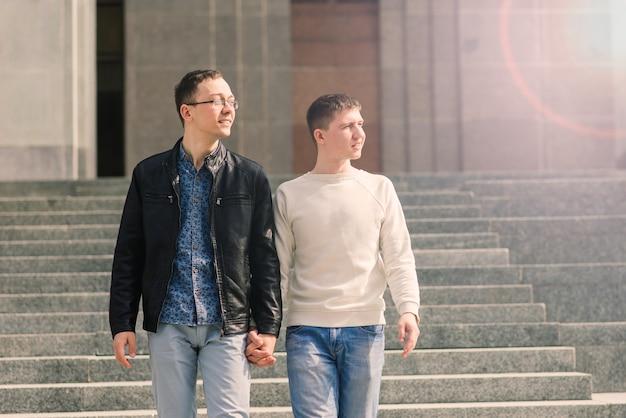 Casal gay caminhando no centro de uma cidade, estilo de vida