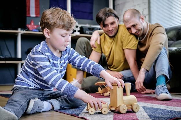 Casal gay casado e feliz olhando para o filho brincando com brinquedos no chão