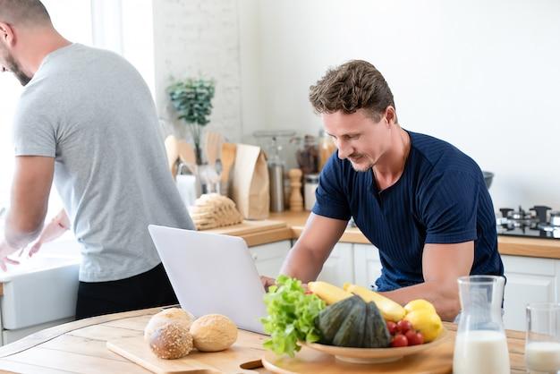 Casal gay caucasiano masculino, trabalhando em casa