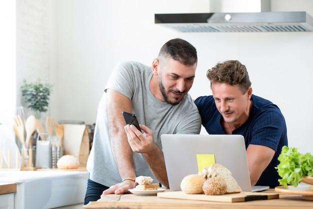 Casal gay caucasiano masculino usando o computador portátil em casa