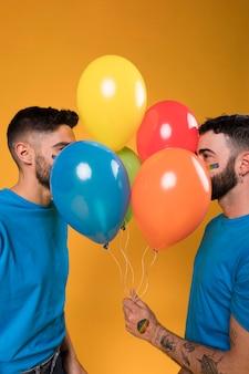 Casal gay com balões de arco-íris