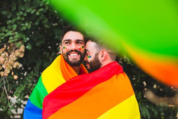 Casal gay com bandeira de arco-íris abraçando na rua