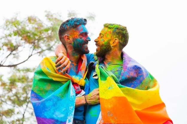 Casal gay com caras pintadas, regozijando-se e abraçando