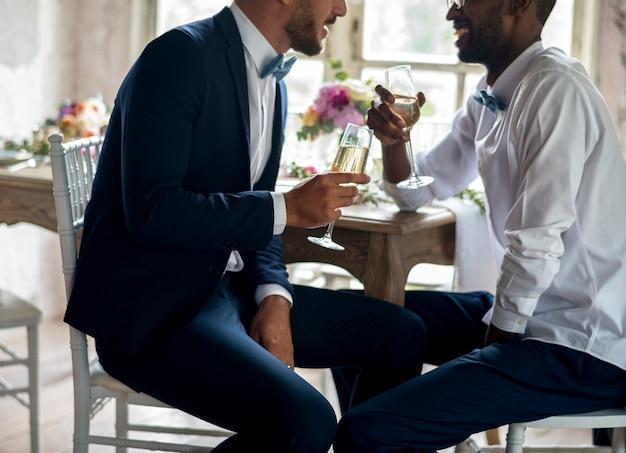Casal gay com champanhe na recepção do casamento