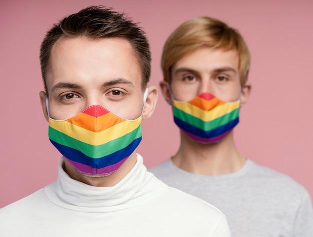 Casal gay com máscara médica arco-íris