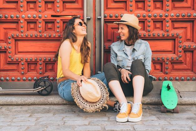 Casal gay de mulheres jovens, olhando e sorrindo um ao outro em uma porta vermelha