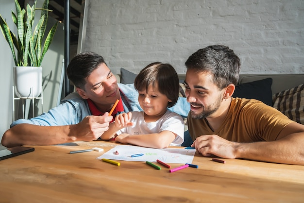 Casal gay e seu filho se divertindo juntos enquanto desenham algo em um papel em casa. conceito de família.