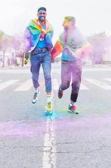 Casal gay em pó de holi multicolorido correndo estrada