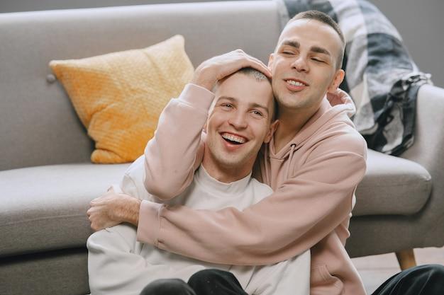 Casal gay em seu apartamento. abraçando e sentando no chão. homossexual.