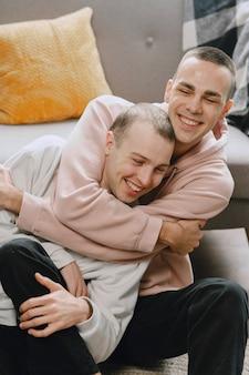 Casal gay em seu apartamento, se abraçando e sentando no chão
