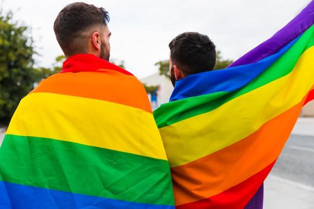Casal gay envolto em bandeiras lgbt em pé atrás