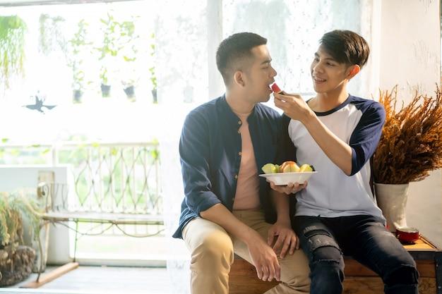 Casal gay está comendo frutas com seu namorado.