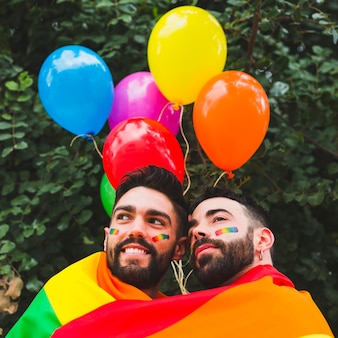 Casal gay feliz com balões lgbt abraçando no jardim