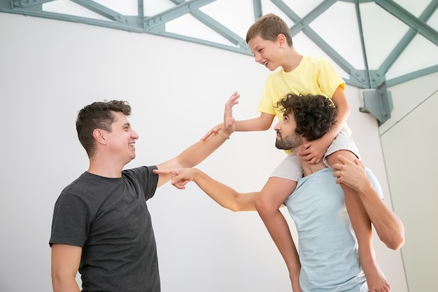 Casal gay feliz e seu filho alegre se divertindo em casa, jogando jogos ativos. rapaz cavalgando no pescoço do homem e. conceito de família e paternidade