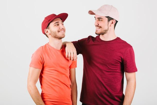 Casal gay feliz em caps em pé perto
