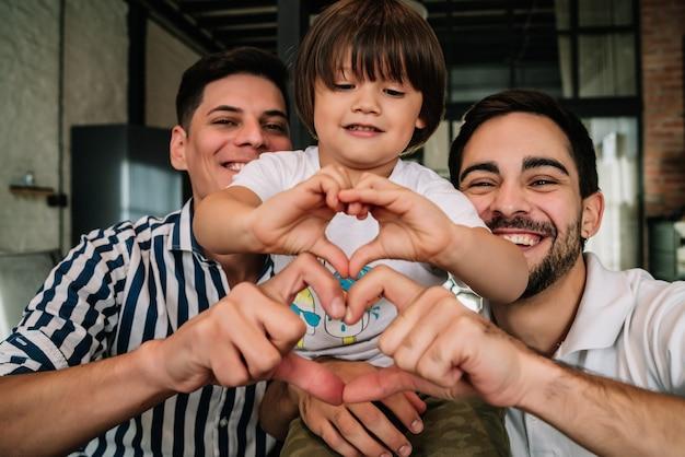Casal gay feliz posando com seu filho ao fazer um formato de coração com as mãos, mostrando amor. conceito de família.