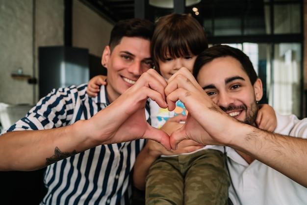 Casal gay feliz posando com seu filho ao fazer um formato de coração com as mãos, mostrando amor.