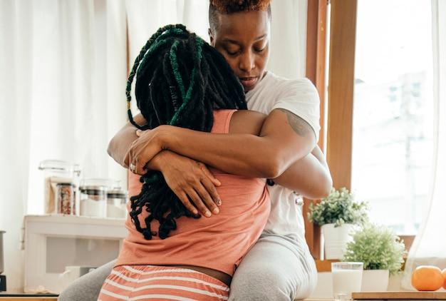 Casal gay feliz se abraçando na cozinha
