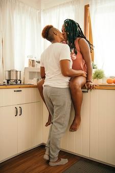 Casal gay feliz se beijando na cozinha