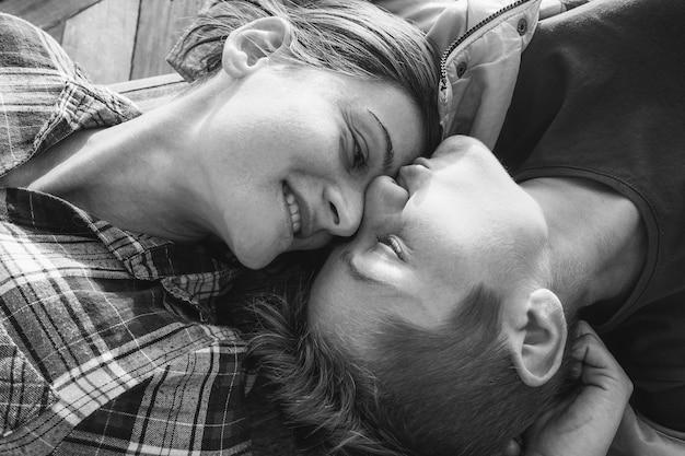Casal gay feliz tendo momentos ternos ao ar livre - mulheres jovens tendo um encontro - direito de igualdade, estilo de vida homossexual, lgbt e conceito de relacionamento - foco principal nos rostos - edição em preto e branco