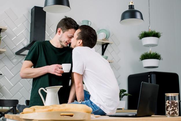 Casal gay feliz tomando café na cozinha e usando o laptop. gays amorosos se beijando, cara a cara enquanto passam o lazer em casa
