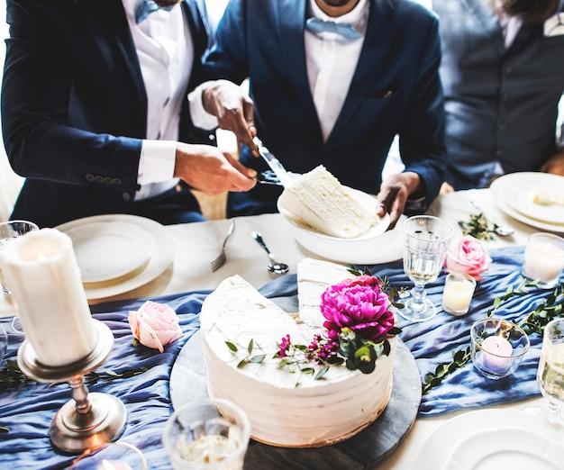 Casal gay mãos cortar bolo de casamento