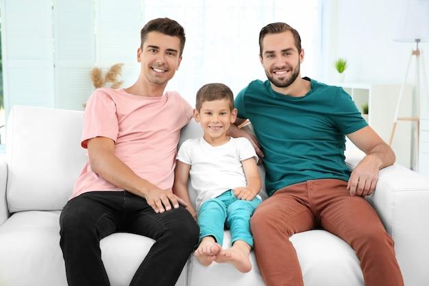 Casal gay masculino com filho adotivo, sentado no sofá em casa. conceito de adoção