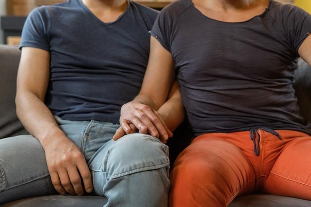 Casal gay masculino irreconhecível de mãos dadas. foco nas mãos