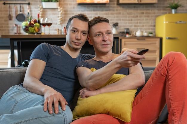 Casal gay masculino sentado no sofá assistindo tv