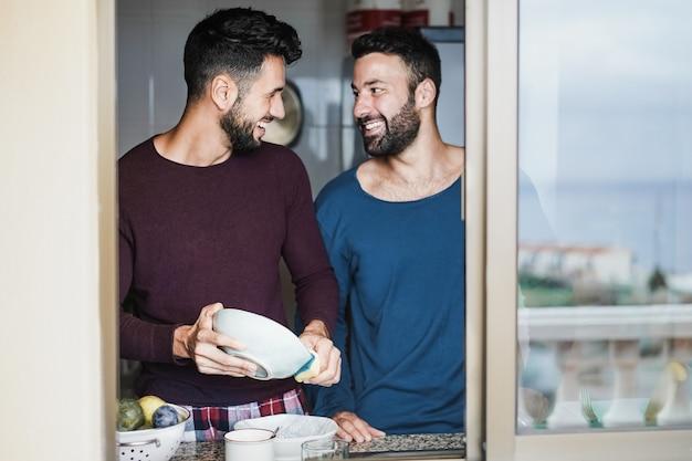 Casal gay masculino tendo momentos de ternura enquanto lava pratos na cozinha de casa - foco no rosto do homem esquerdo