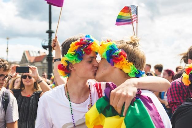 Casal gay se beijando no meio da multidão no desfile lgbt
