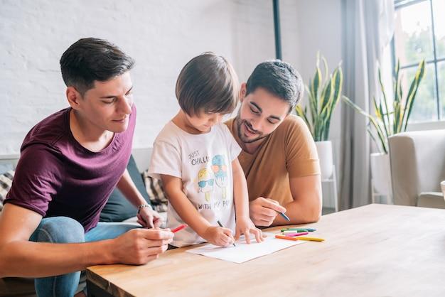 Casal gay se divertindo com seu filho em casa.