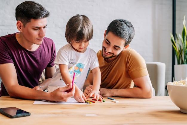 Casal gay se divertindo com seu filho enquanto desenha algo em um papel em casa. conceito de família.