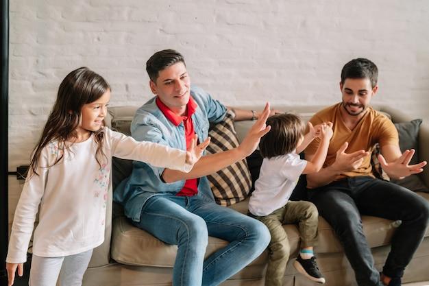 Casal gay se divertindo enquanto brincava com seus filhos em casa. conceito de família.