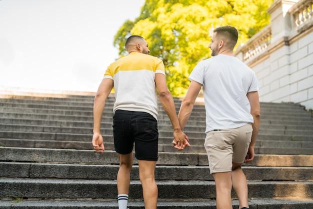 Casal gay segurando suas mãos e andando.