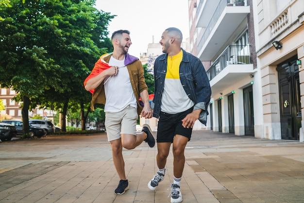 Casal gay segurando suas mãos e correndo juntos