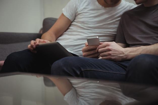 Casal gay sentado no sofá olhando para tablet digital