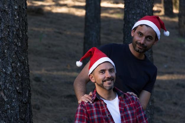 Casal gay sorridente com chapéus vermelhos de natal posando no parque florestal. homens felizes comemoram o feriado de inverno