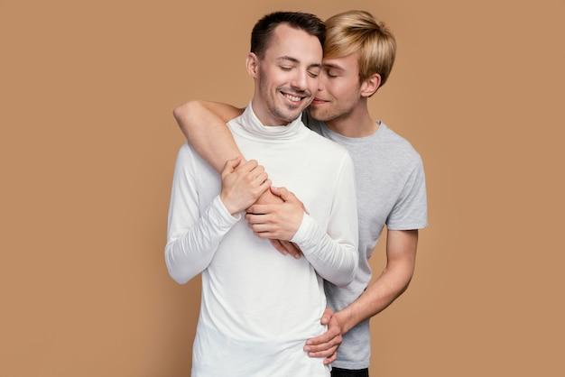 Casal gay sorridente com símbolo lgbt