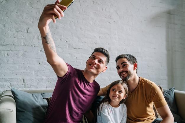 Casal gay tirando uma selfie com sua filha enquanto está sentado em um sofá juntos em casa. conceito de família.