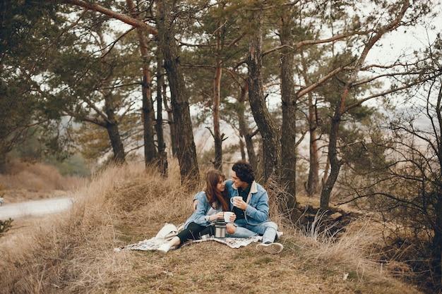Casal gentil e elegante, sentado no parque outono e beber um chá