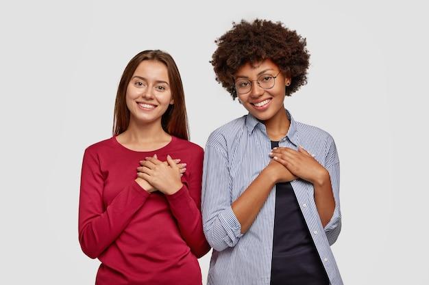 Casal gentil mantém ambas as mãos no peito, expressa gratidão