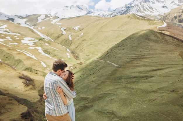 Casal georgiano apaixonado abraça o fundo de altas montanhas